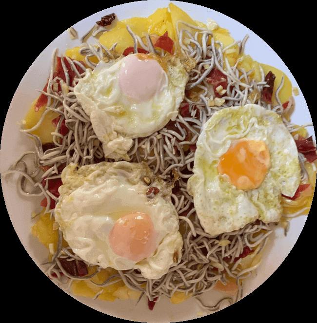 Huevos rotos al plato con patatas frita, gulas, jamón serrano y huevos fritos.