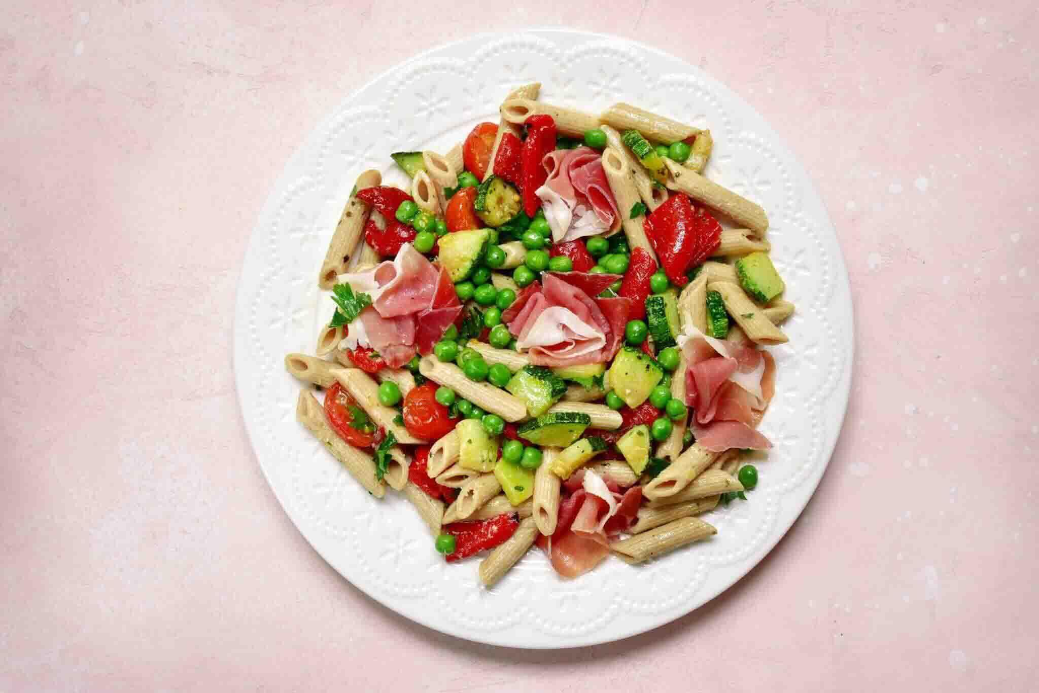Plato de pasta con calabacín, guisantes, tomate y jamón. Receta fácil.